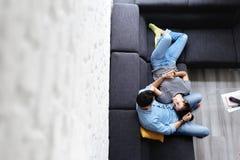 Junge Paare, die auf Sofa umarmen und lachen lizenzfreie stockbilder