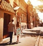 Junge Paare, die auf Straße im Sommer des sonnigen Tages gehen stockbilder