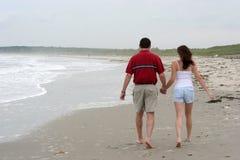 Junge Paare, die auf Strand gehen Stockbilder