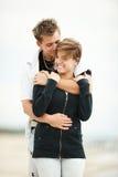 Junge Paare, die auf Strand küssen Lizenzfreie Stockfotografie