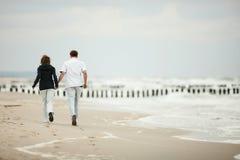 Junge Paare, die auf Strand laufen Stockfotos
