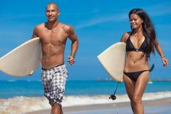 Junge Paare, die auf Strand laufen Lizenzfreies Stockfoto