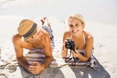 Junge Paare, die auf Strand liegen stockbild