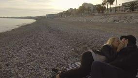 Junge Paare, die auf Strand liegen und, Frau küsst Mann, liebevolles Verhältnis sprechen stock video footage