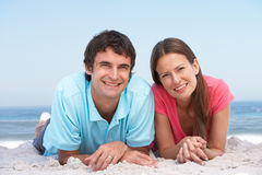 Junge Paare, die auf Strand sich entspannen Stockbilder