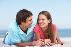 Junge Paare, die auf Strand sich entspannen Lizenzfreies Stockbild