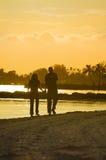 Junge Paare, die auf Strand am Sonnenuntergang gehen Lizenzfreie Stockfotografie