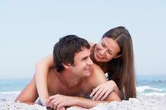 Junge Paare, die auf Strand-tragender Badebekleidung sich entspannen Lizenzfreie Stockbilder