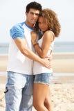 Junge Paare, die auf Strand umfassen Stockbild