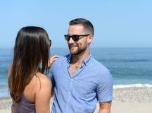Junge Paare, die auf Strand umfassen Stockbilder