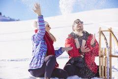 Junge Paare, die auf Sunny Winter Day rodeln und genießen Lizenzfreie Stockfotos
