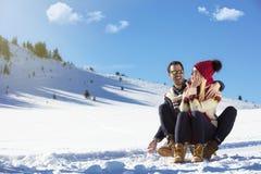 Junge Paare, die auf Sunny Winter Day rodeln und genießen Stockfotos