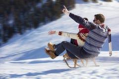 Junge Paare, die auf Sunny Winter Day rodeln und genießen Stockbild