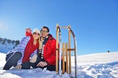 Junge Paare, die auf Sunny Winter Day rodeln und genießen Stockbilder