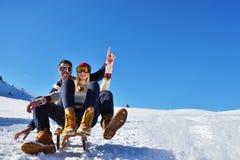 Junge Paare, die auf Sunny Winter Day rodeln und genießen Stockfotografie