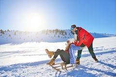Junge Paare, die auf Sunny Winter Day rodeln und genießen Lizenzfreie Stockfotografie