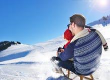 Junge Paare, die auf Sunny Winter Day rodeln und genießen Stockfoto