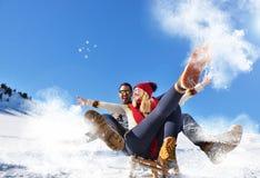 Junge Paare, die auf Sunny Winter Day rodeln und genießen Lizenzfreie Stockbilder