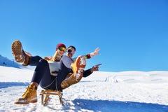 Junge Paare, die auf Sunny Winter Day rodeln und genießen Lizenzfreies Stockfoto