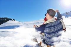 Junge Paare, die auf Sunny Winter Day rodeln und genießen Lizenzfreies Stockbild
