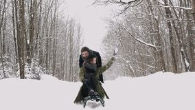 Junge Paare, die auf Sunny Winter Day rodeln und genießen Langsame Bewegung stock video footage