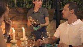 Junge Paare, die auf Tabelle mit Kerze während romantisches Abendessen im Restaurant sitzen Trinkender Wein des Mannes und der Fr stock footage