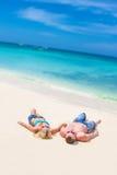 Junge Paare, die auf tropischem Strand des Sandes auf blauem Himmel sich entspannen Lizenzfreie Stockfotos