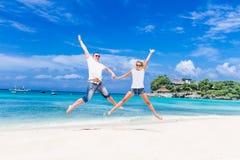 Junge Paare, die auf tropischem Strand des Sandes auf blauem Himmel sich entspannen Lizenzfreie Stockfotografie