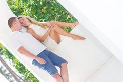 Junge Paare, die auf tropischem Strand des Sandes auf blauem Himmel sich entspannen Lizenzfreies Stockfoto