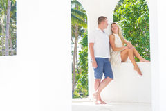 Junge Paare, die auf tropischem Strand des Sandes auf blauem Himmel sich entspannen Lizenzfreies Stockbild