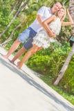 Junge Paare, die auf tropischem Strand des Sandes auf blauem Himmel sich entspannen Lizenzfreie Stockbilder