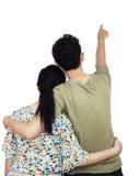 Junge Paare, die auf Wand zeigen Stockbilder