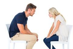 Junge Paare, die bei der Stuhlargumentierung sitzen Lizenzfreie Stockfotografie