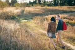 Junge Paare, die bei Sonnenuntergang gehen Lizenzfreies Stockbild