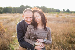 Junge Paare, die bei Sonnenuntergang umarmen Stockbilder