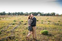 Junge Paare, die bei Sonnenuntergang umarmen Stockfotografie