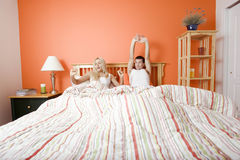 Junge Paare, die beim Bett-Ausdehnen liegen Lizenzfreie Stockfotografie