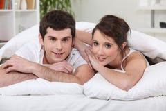 Junge Paare, die in Bett legen stockfoto