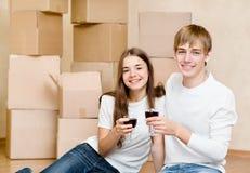 Junge Paare, die das Bewegen auf neues Haus feiern Stockfotos