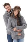 Junge Paare, die das gleiche Strickjackelächeln tragen Lizenzfreie Stockbilder