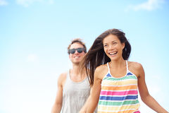 Junge Paare, die das lachende Laufen des Strandspaßes genießen Stockfoto