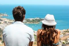 Junge Paare, die das Meer sitzen und betrachten lizenzfreie stockfotos
