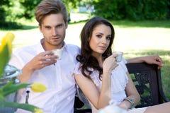 Junge Paare, die das Mittagessen im Garten genießen stockfotos