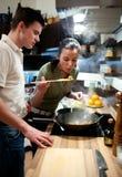 Junge Paare, die das Mittagessen vorbereiten Stockfotos