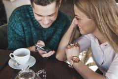 Junge Paare, die das Netz an betrachtet Fotos surfen Stockfotografie