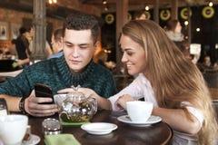 Junge Paare, die das Netz an betrachtet Fotos surfen Stockbilder