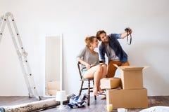 Junge Paare, die in das neue Haus, Fotos machend sich bewegen Lizenzfreies Stockbild