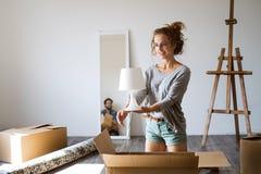 Junge Paare, die in das neue Haus, Kästen auspackend sich bewegen lizenzfreies stockbild