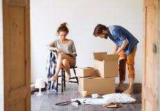 Junge Paare, die in das neue Haus, Sachen auspackend sich bewegen lizenzfreies stockfoto