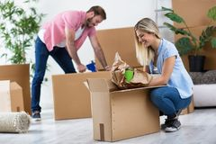 Junge Paare, die in das neue Haus, Sachen auspackend sich bewegen lizenzfreie stockfotos